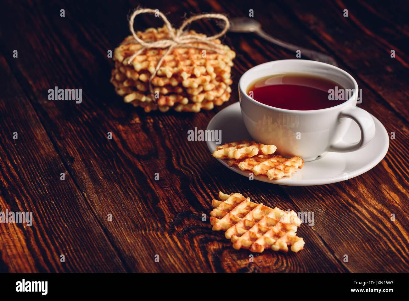 Dessert with White Cup of Tea and Waffle Stack and Waffles Pieces. Copy Space on the Left. - Stock Image