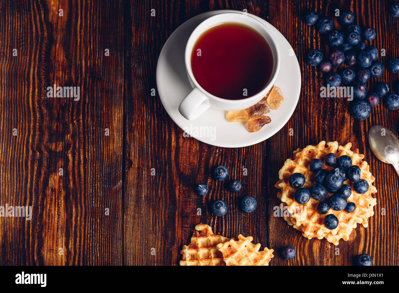 White Cup of Tea with Blueberry and Homemade Waffles on Wooden Background. Copy Space on the Left. - Stock Image