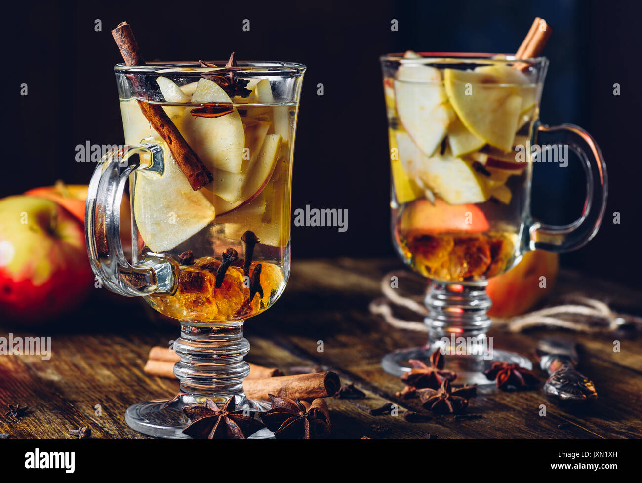 Two Glasses of Christmas Spiced Beverage with Sliced Apple, Clove, Cinnamon, Anise Star and Dark Candy Sugar. All Ingredients and Some Kitchen utensil - Stock Image