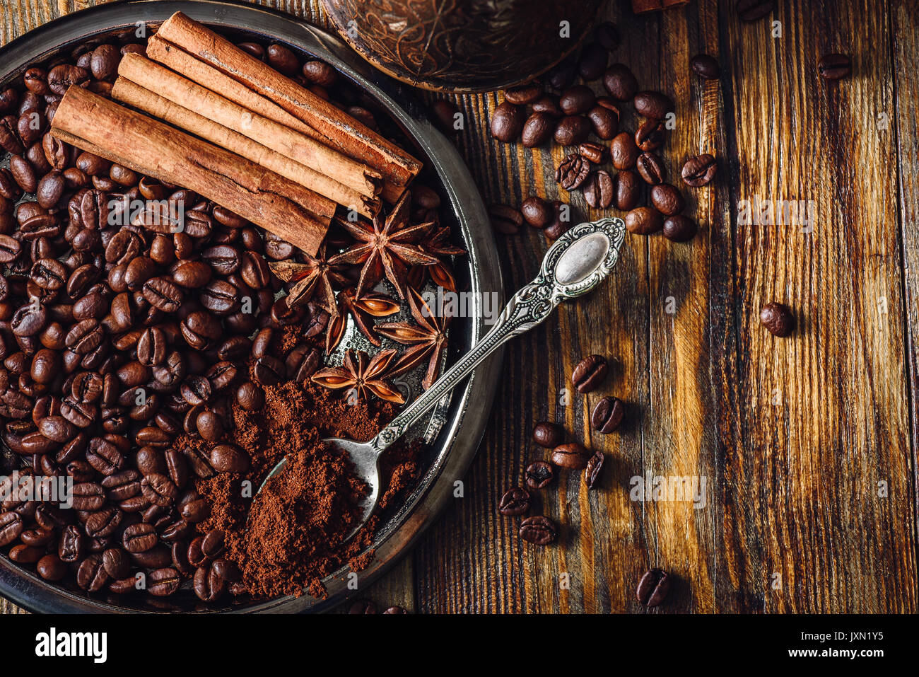 Coffee Beans with Spooonful of Ground Coffee, Cinnamon Sticks and Chinese Star Anise on Metal Plate. Some Beans Scattered on Wooden Table. View from A - Stock Image