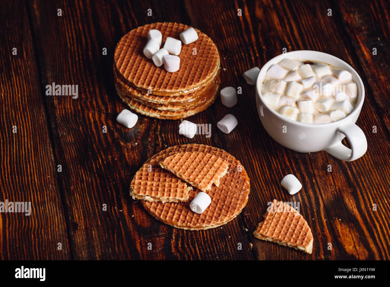 Stroopwafel with Broken One with White Cup of Cocoa with Marshmallow and Waffle Stack. Copy Space on the Left. - Stock Image