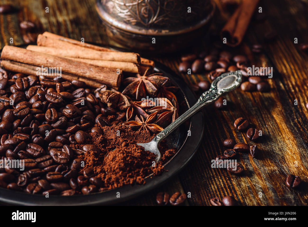 Coffee Beans with Spooonful of Ground Coffee, Cinnamon Sticks and Chinese Star Anise on Metal Plate. Some Beans Scattered on Wooden Table and Cezve on - Stock Image