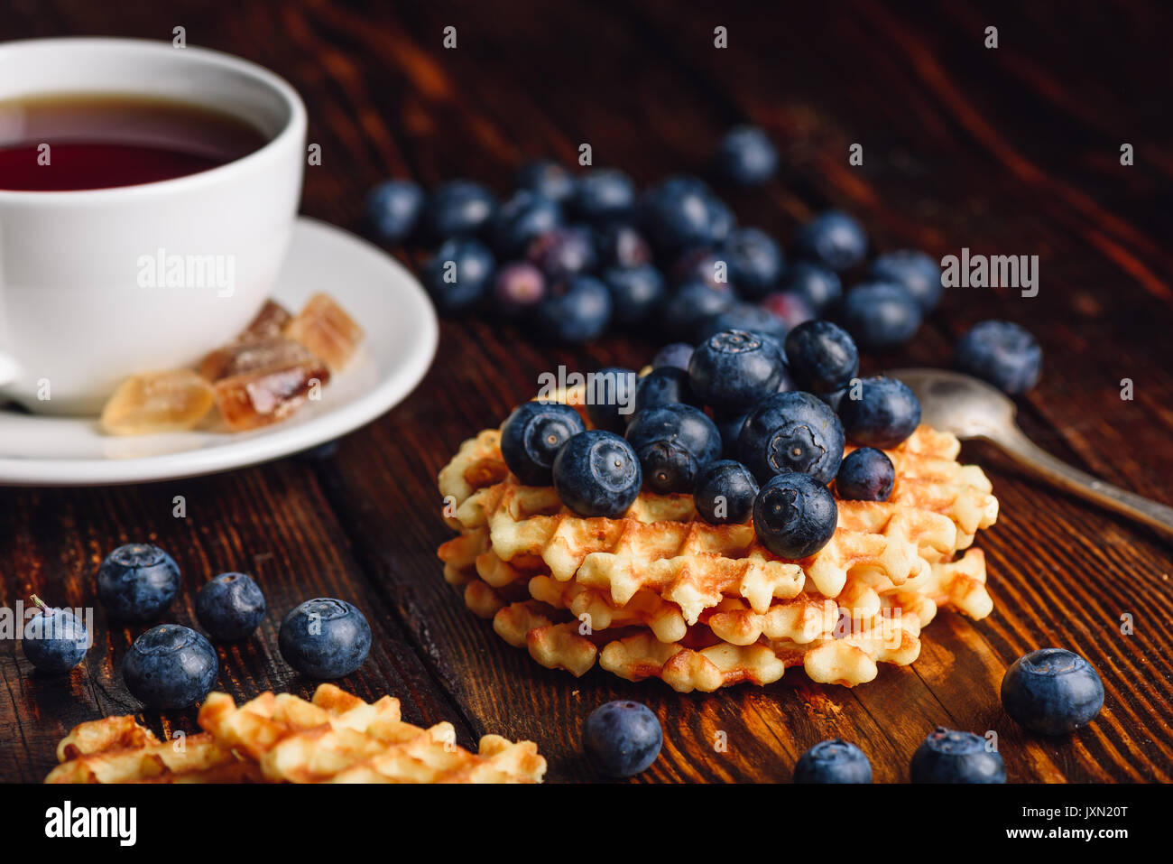 White Cup of Tea with Blueberries and Homemade Waffles for Breakfast. - Stock Image