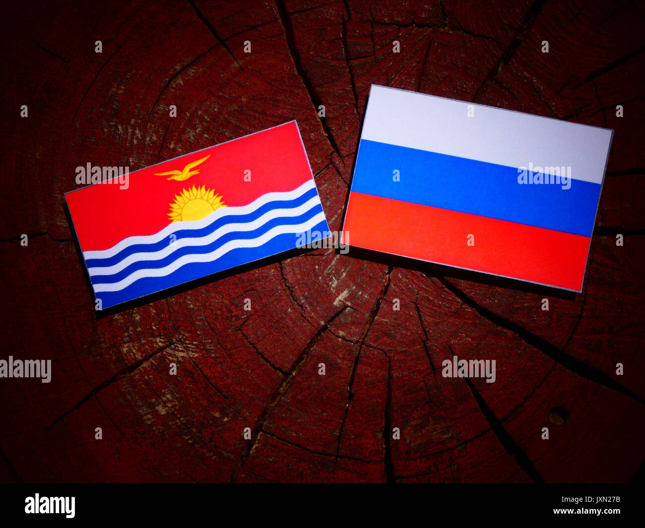 Kiribati flag with Russian flag on a tree stump isolated - Stock Image
