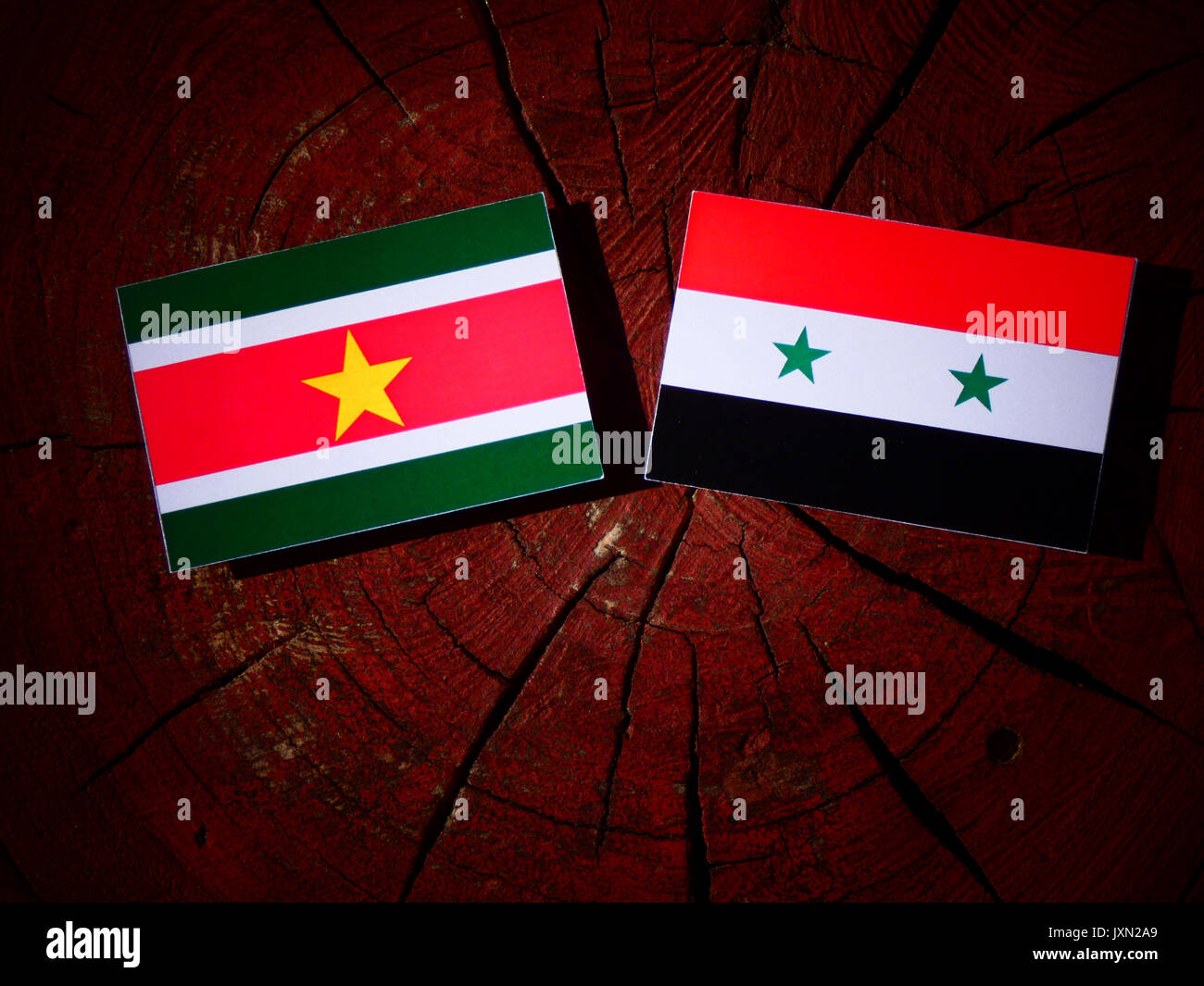 Suriname flag with Syrian flag on a tree stump isolated - Stock Image