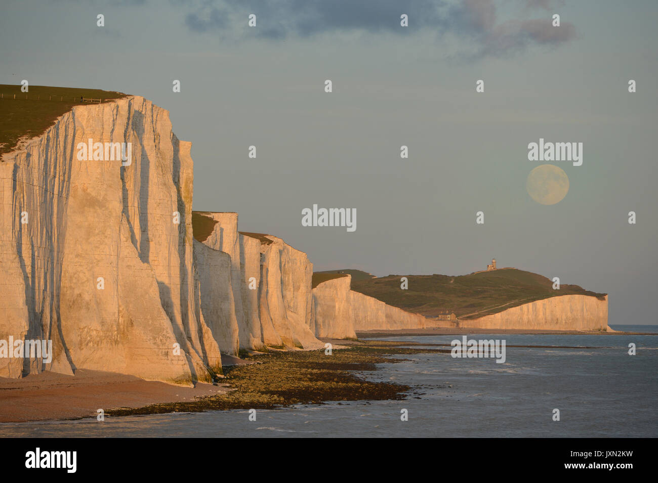 Moon rising over the Seven Sisters chalk cliffs at sunset. - Stock Image