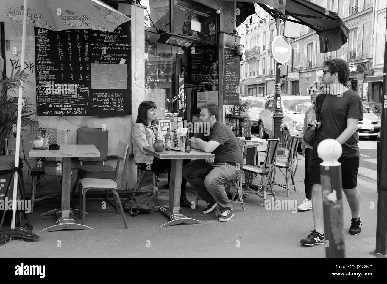 A couple sitting at a pavement table outside a cafe in a Paris suburb Stock Photo