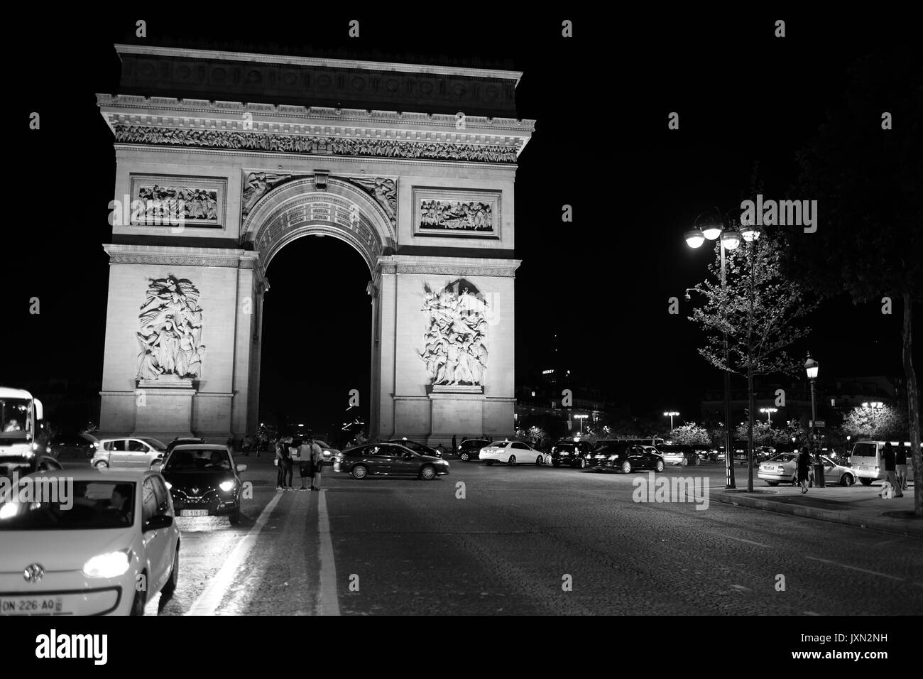 A shot taken at night of The Arc de Triomphe de l'Étoile, one of the most famous monuments in Paris, at the end of the Champs-Élysées - Stock Image