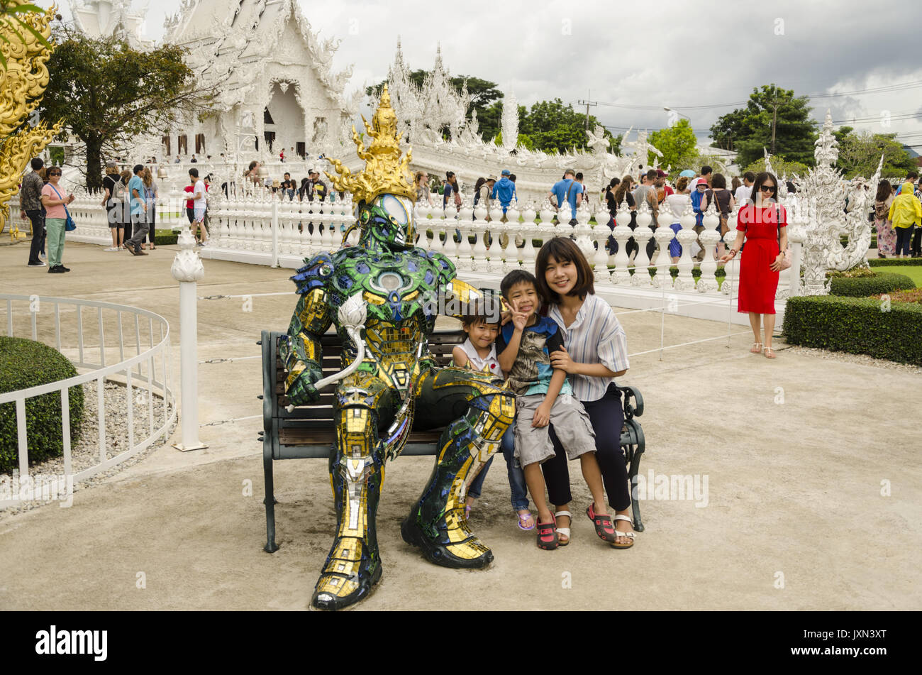 Wat Rong Khun, mother and 2 children sitting on bench with shiny metallic armor covered lifelike statue in front of White Temple, Chiang Rai, Thailand - Stock Image