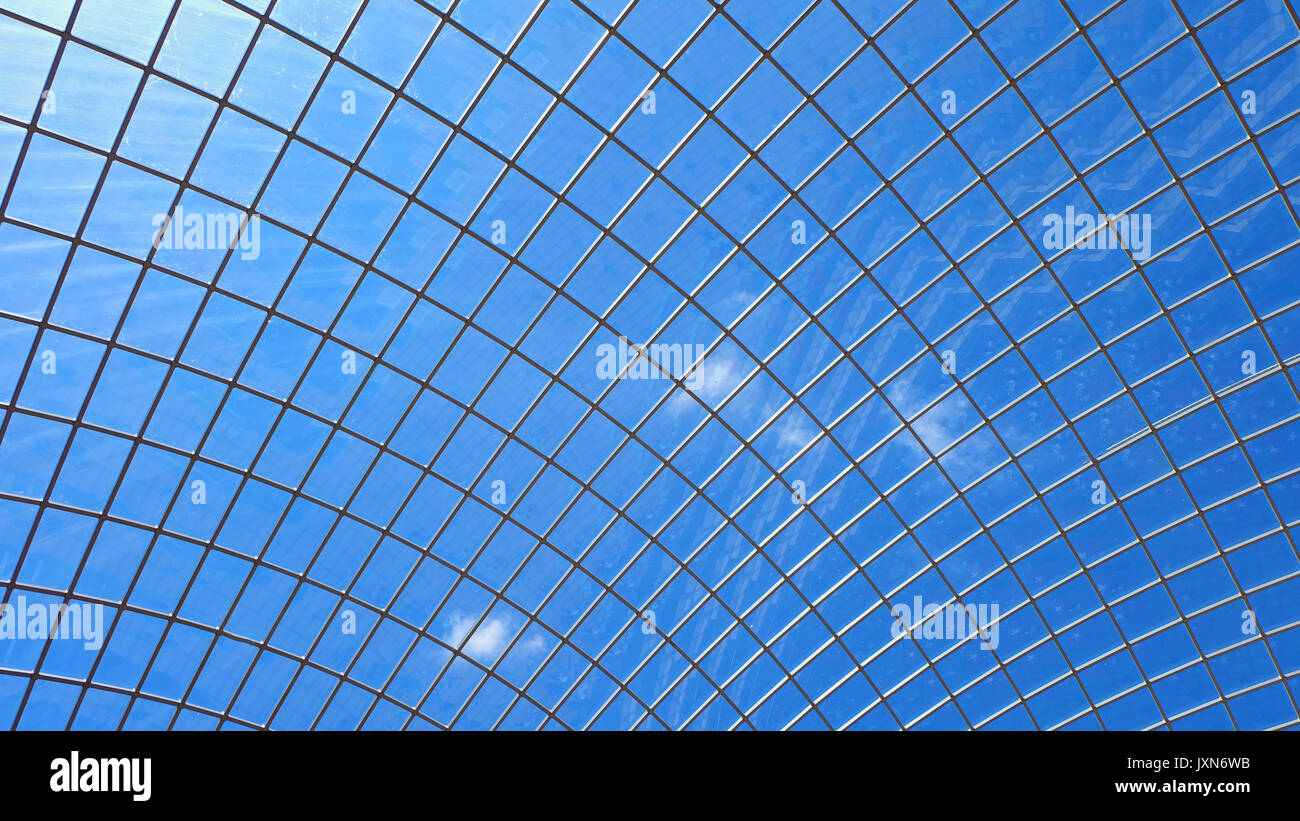 A dome shaped glass ceiling with metal support structure beams or frame with blue sky and a little white clouds in the background. - Stock Image