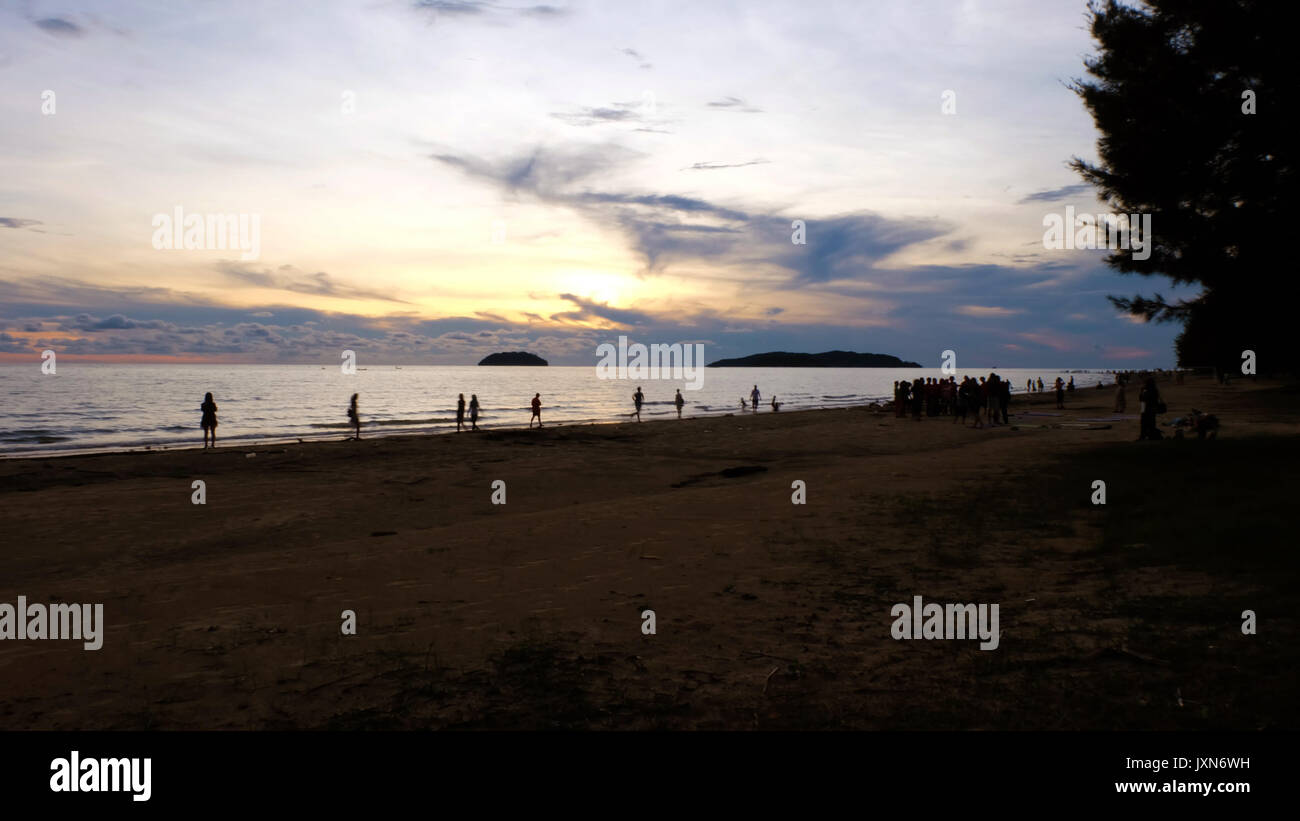 A beach front during sunset, with silhouette of people playing at the beach and enjoying the view. Distant islands in the background. Colorful orange - Stock Image