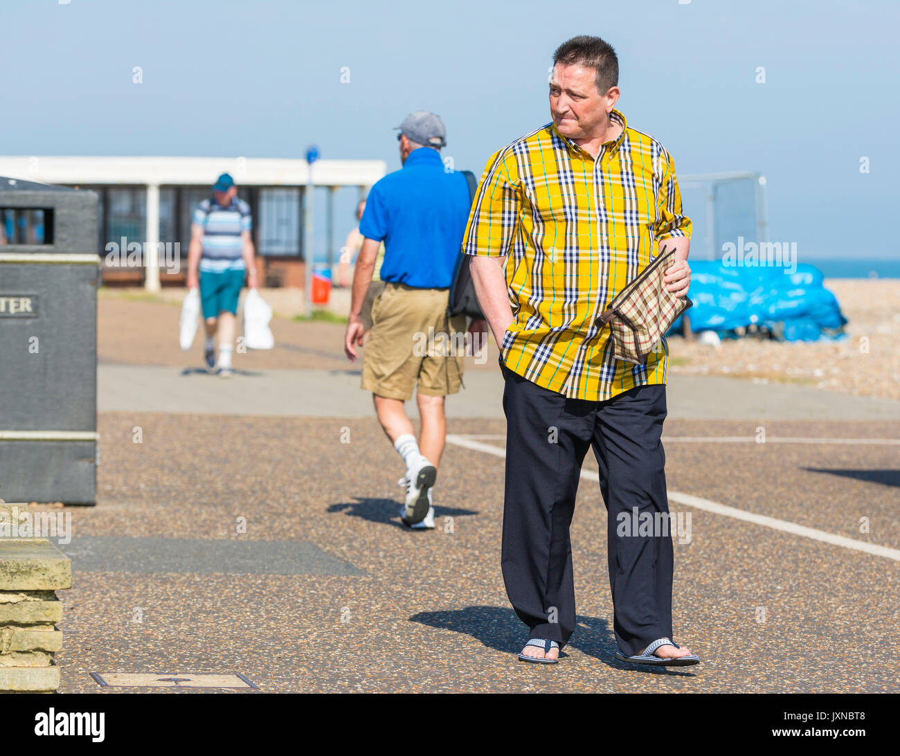 Casually dressed middle aged man walking along a path in Summer wearing sandals. - Stock Image
