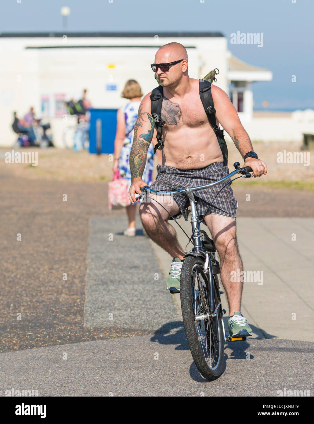 Shirtless man riding a bicycle in Summer on a hot day in the UK. - Stock Image