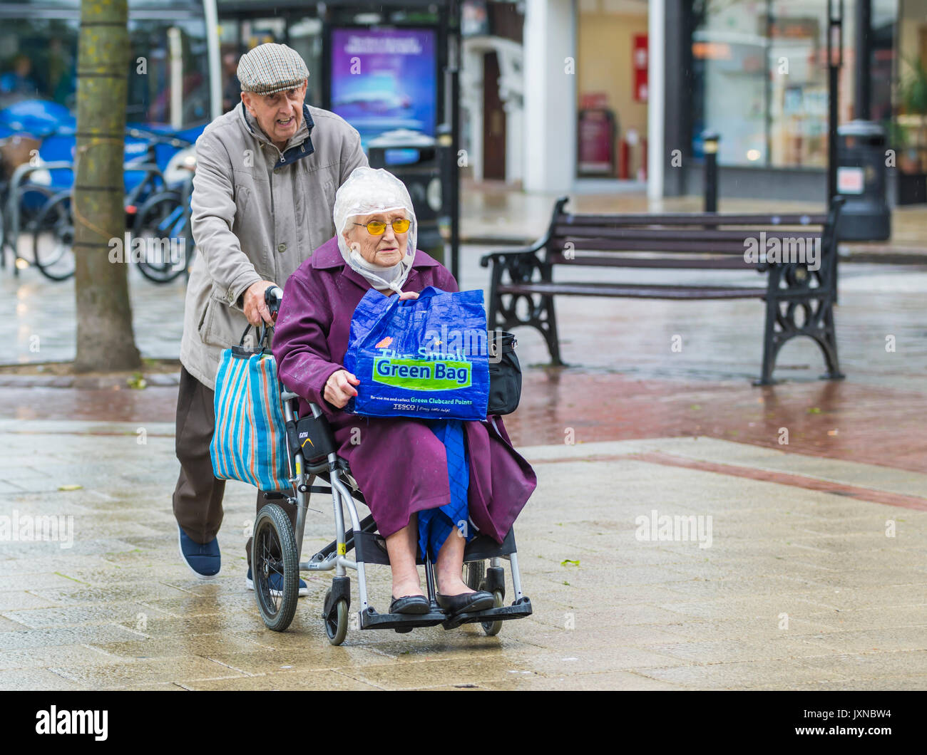 Elderly couple shopping in the rain, one pushing the other in a wheelchair, carrying a Tesco 'bag for life'. 'The small green bag'. Old disabled rain. - Stock Image