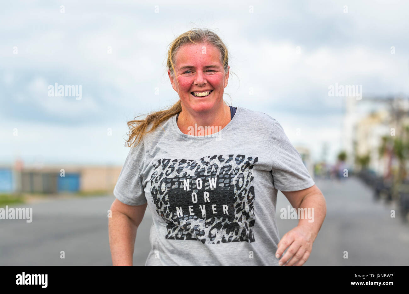 Middle aged overweight woman running as part of plan to lose weight and get fit, at the Worthing Vitality Parkrun event. - Stock Image