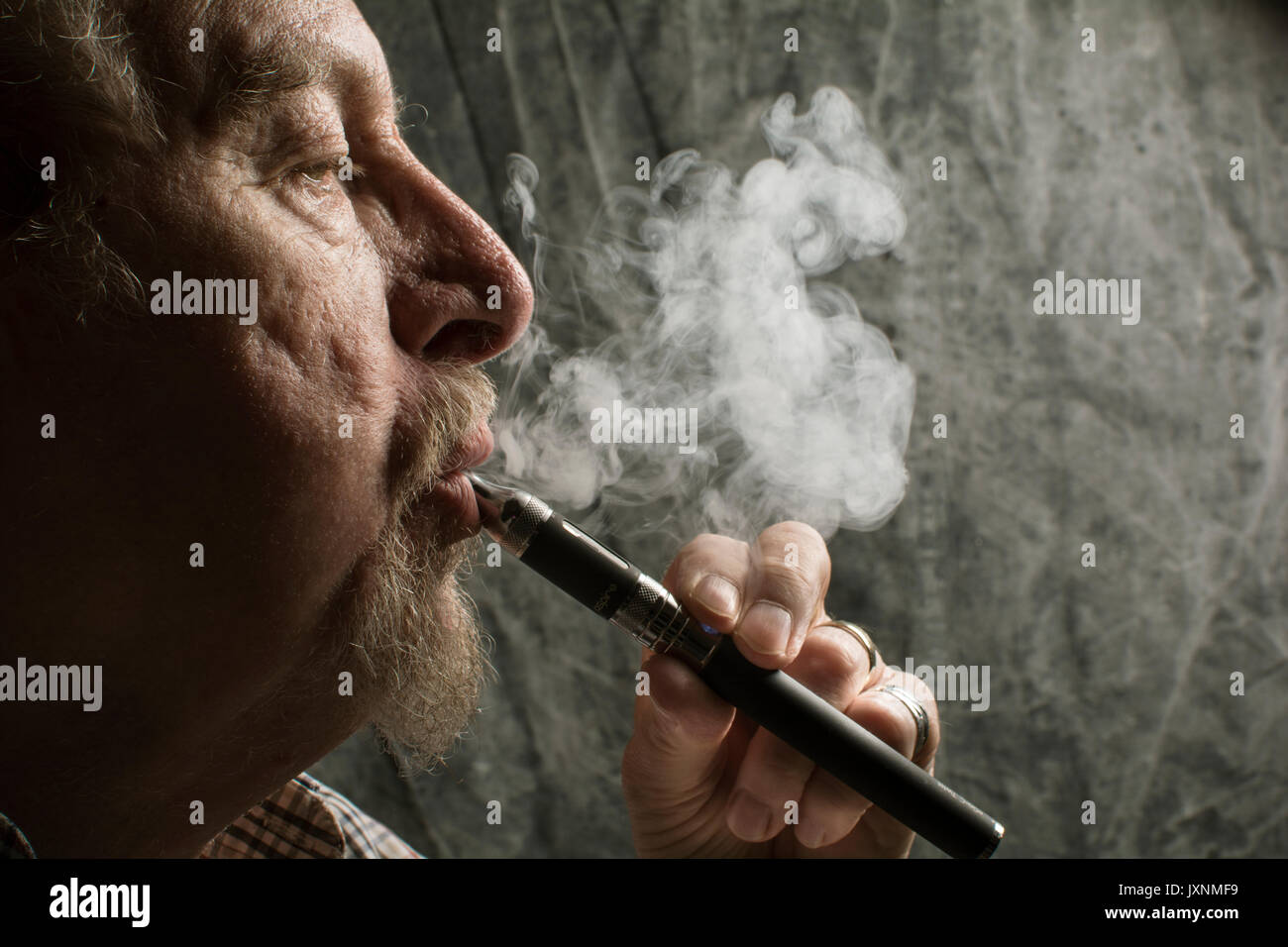 An older man with a beard smoking an electronic cigarette ( vaping an E-cigarette), a healthier option than tobacco - Stock Image