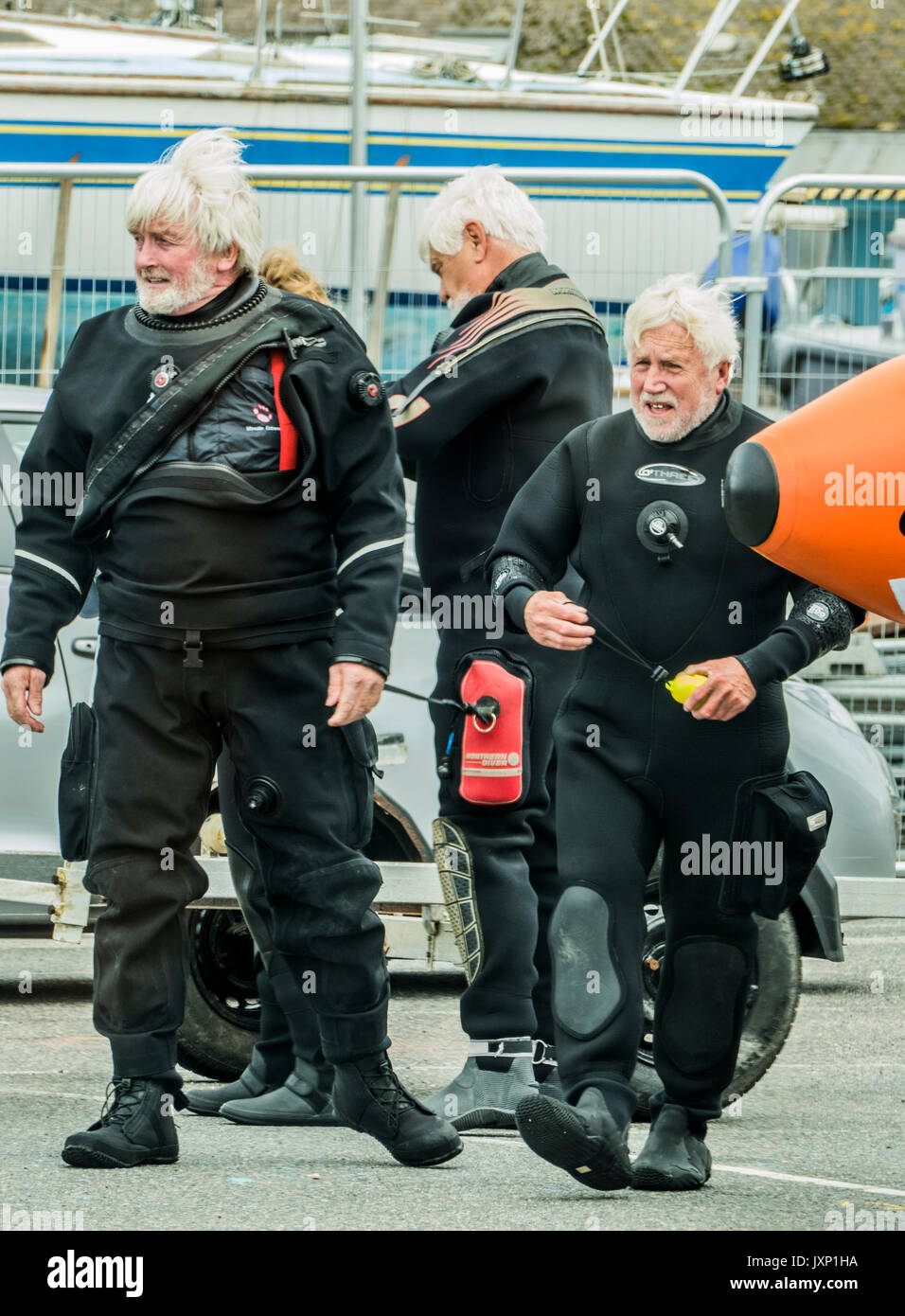 Three elderly male friends in diving suits, in Penzance harbour, Cornwall, England, UK. - Stock Image