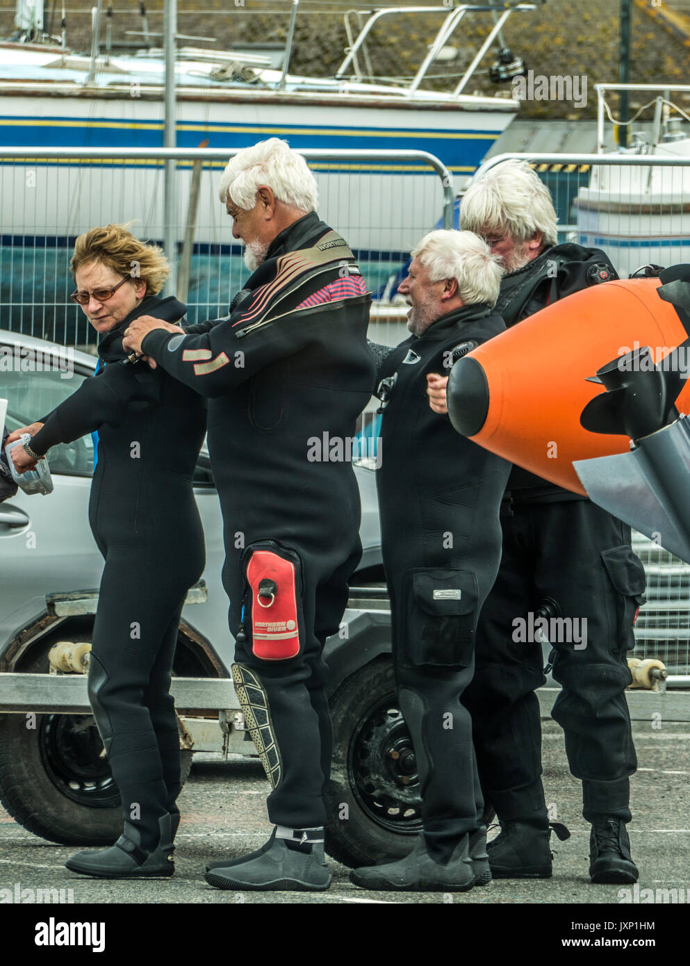 Humorous scene of four elderly friends helping each other with the fitting of their diving suits, in Penzance harbour, Cornwall, England, UK. - Stock Image