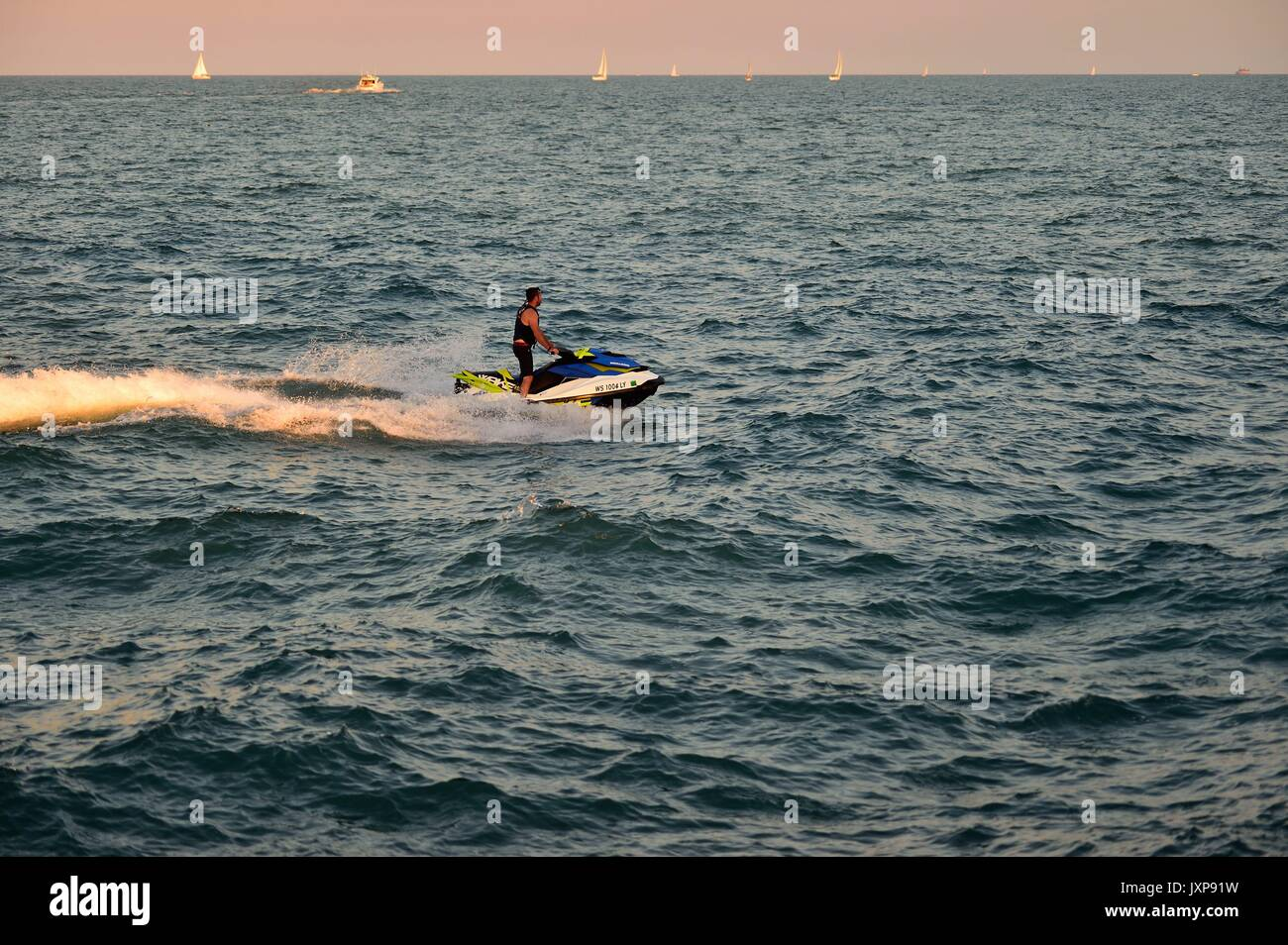 Man piloting a watercraft on Lake Michigan just outside Chicago's Diversey Harbor. Chicago, Illinois, USA. - Stock Image