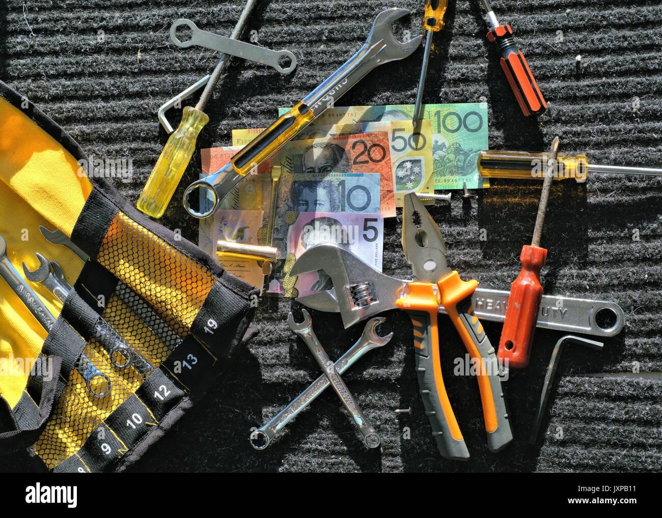Australian money and tools of mechanic on black mat in direct sunlight Stock Photo