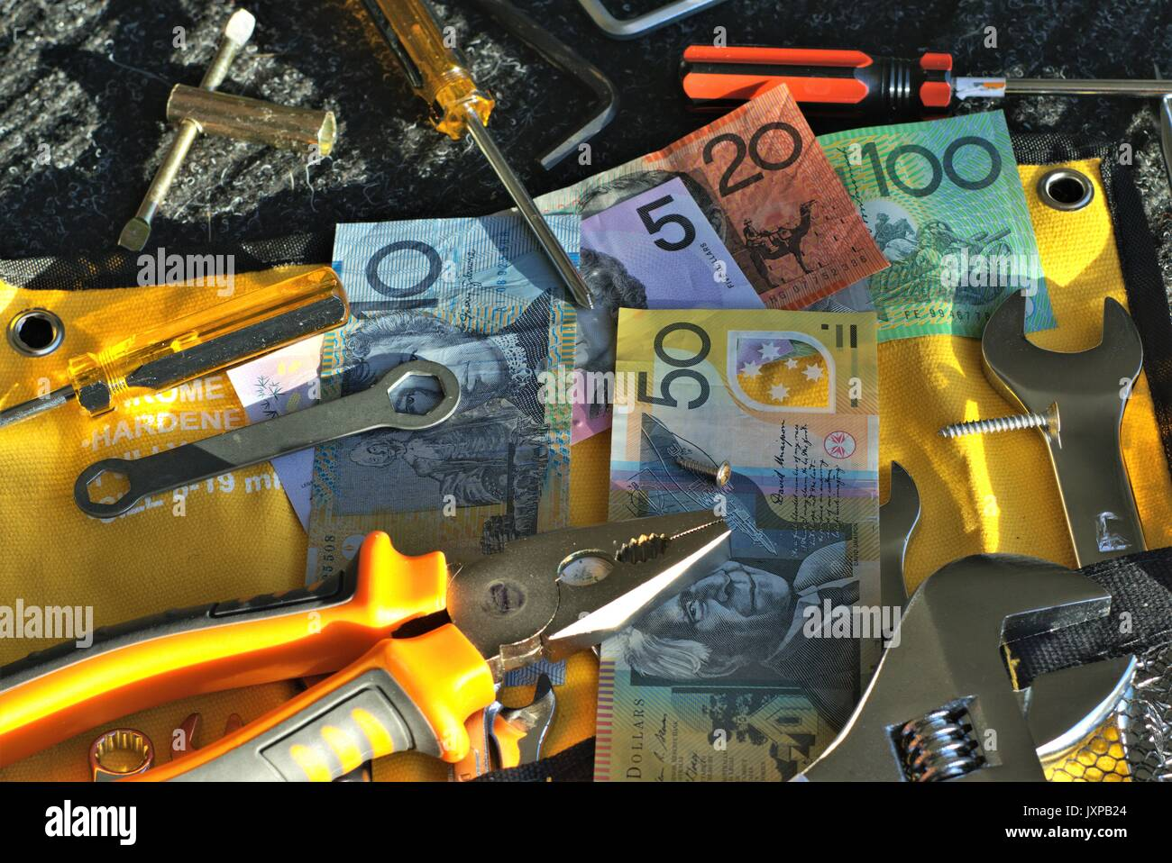 Australian money and tools of mechanic on black mat in direct sunlight - Stock Image