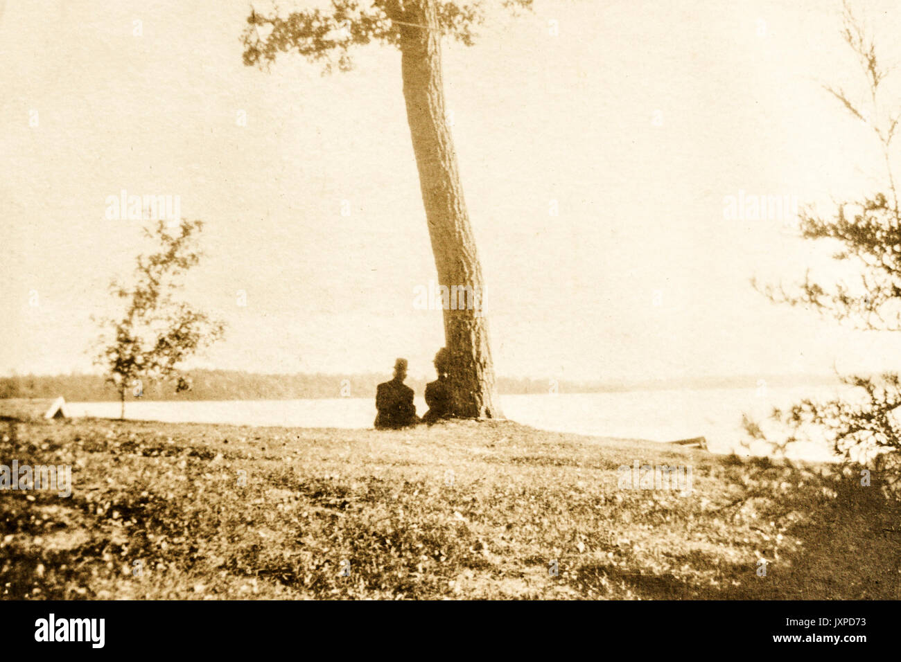 A man and woman sitting under a tree along the shores of Lake Minnetonka  Minnesota 1907-1908 Stock Photo