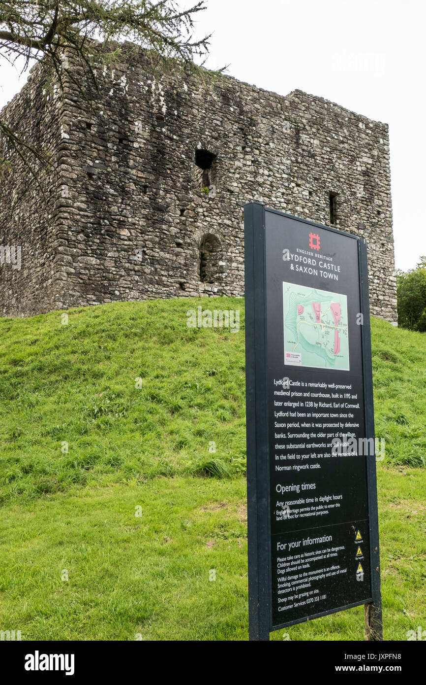 Ancient Lydford Castle sitting high on a mound, with English Heritage sign in the foreground. Lydford near Okehampton, Devon, England, UK. - Stock Image