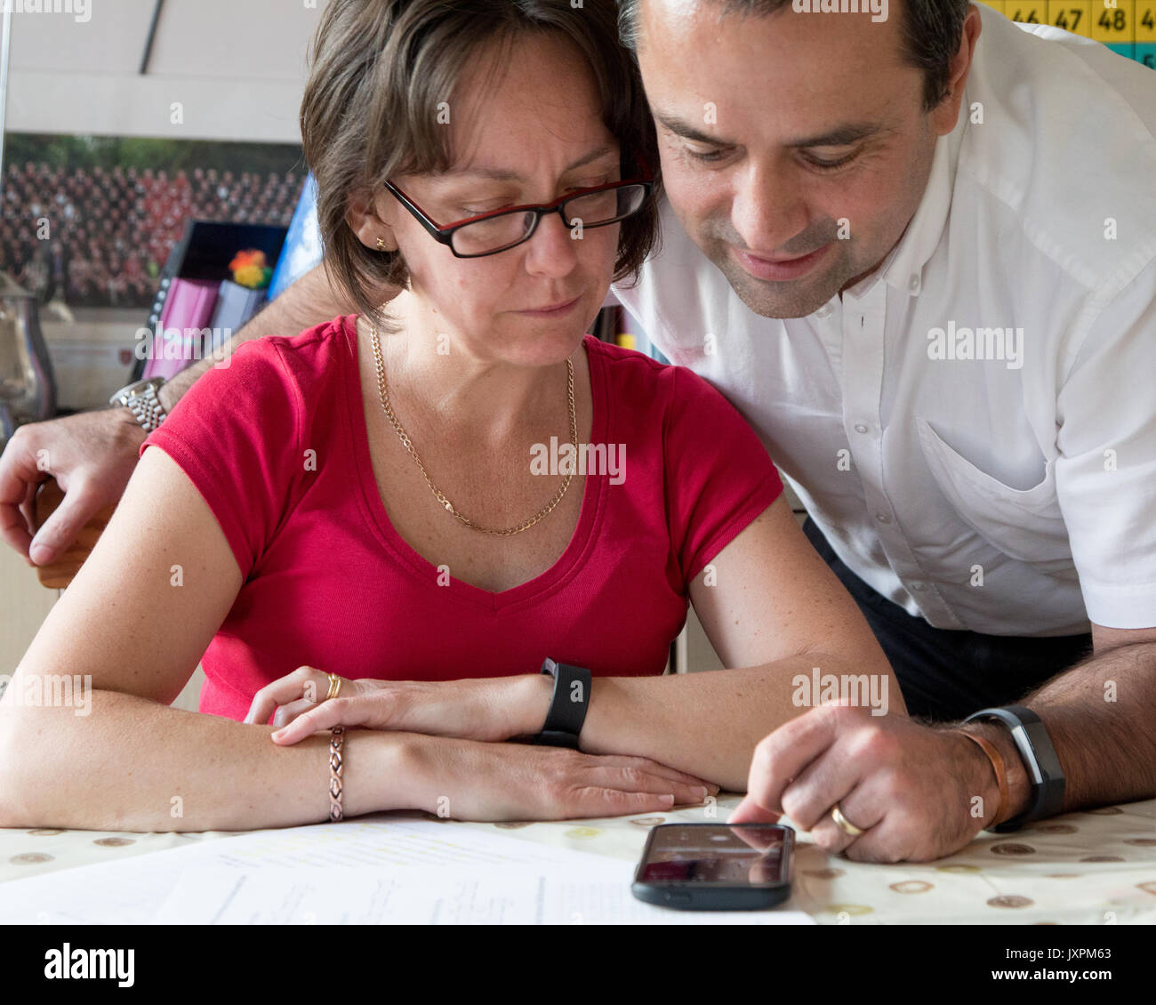 two people looking at paperwork and mobile phone Stock Photo