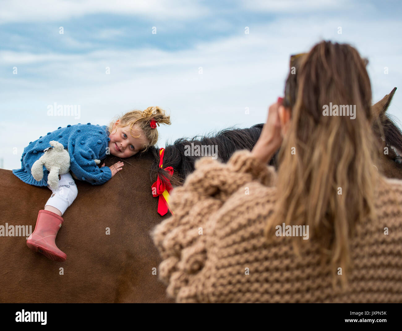 Little girl being photographed on a horse - Stock Image