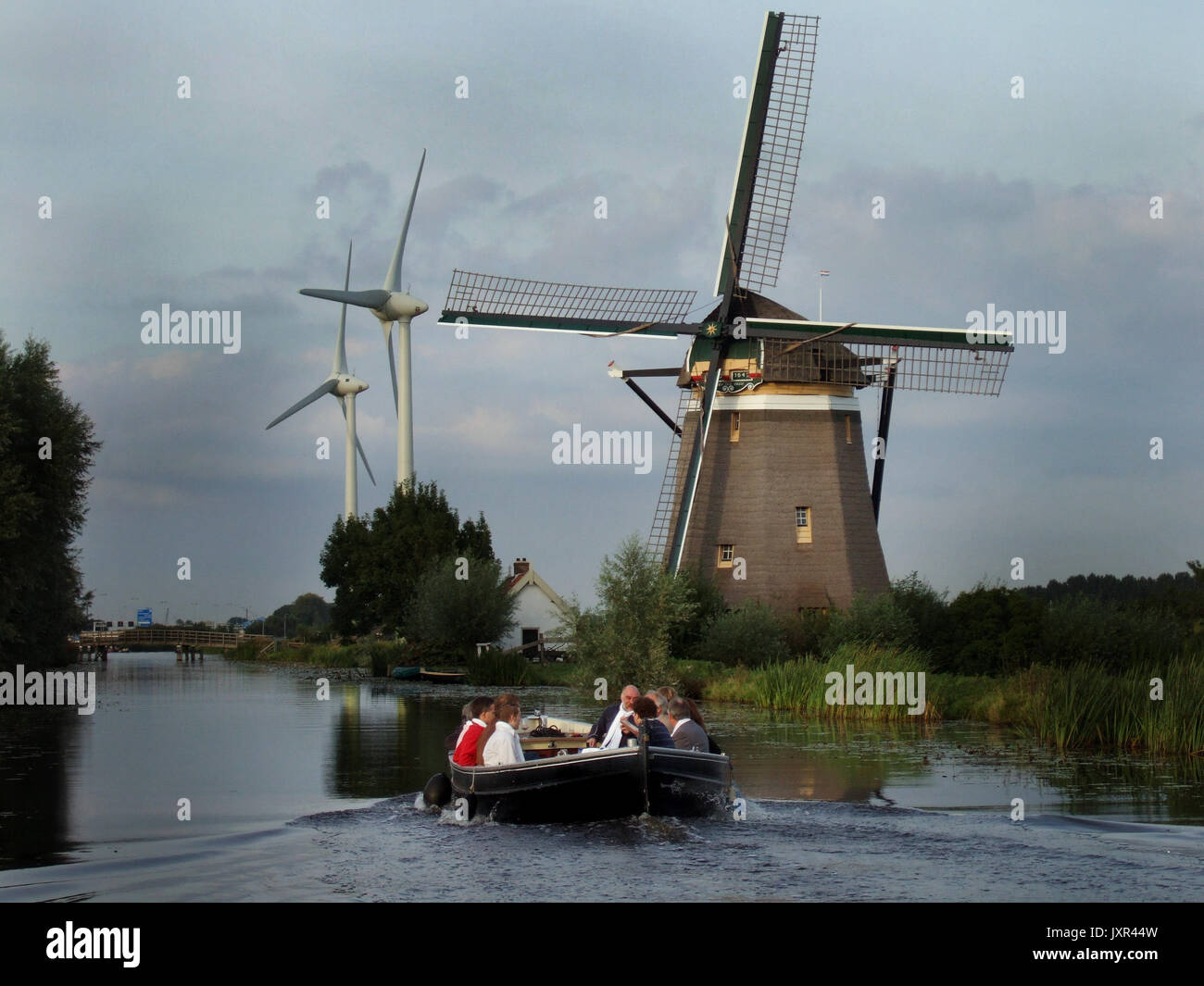 Wind turbines side by side with traditional Dutch windmill near Leiden Netherlands August 12th 2016  Wind energy or wind power describes the process by which wind is used to generate electricity. Wind turbines convert the kinetic energy in wind to electricity by rotating propeller-like blades around a rotor. The rotor turns the drive shaft, which turns an electric generator. Three key factors affect the amount of energy a turbine can harness from the wind: wind speed, air density, and swept area. Renewable energy is energy that is collected from renewable resources, which are naturally repleni - Stock Image