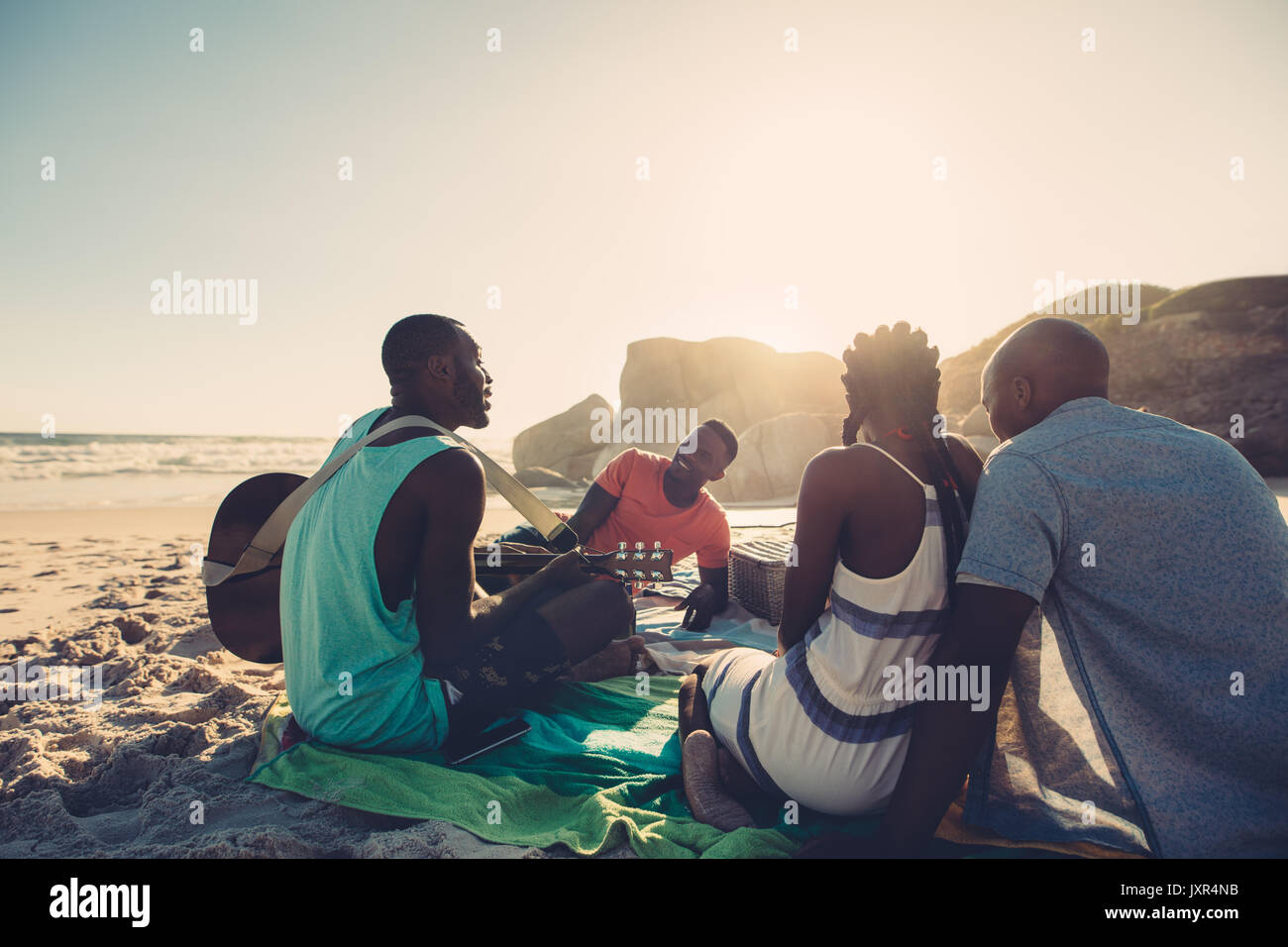 African young man singing and playing guitar on the beach. Group of four people having great time at the beach picnic. - Stock Image
