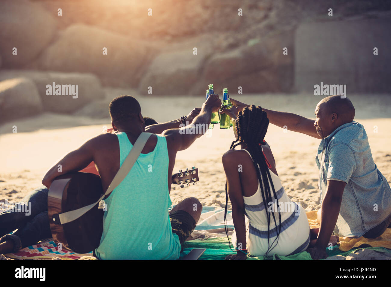Young people toasting with beer bottles while sitting on beach. Group of friends having drinks together. - Stock Image