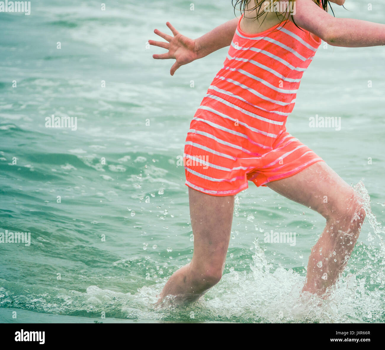Retro Style Detail Of A Child In Old Fashioned Swimsuit Playing In The Ocean Waves Stock Photo