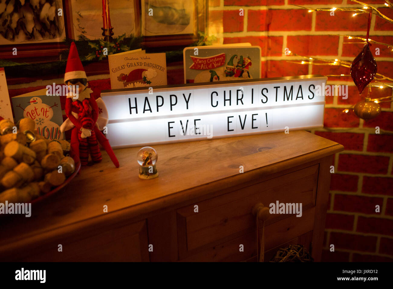 Lightbox reading 'Happy Christmas Eve Eve' on top of chest, surrounded by Christmas cards and paraphernalia. - Stock Image