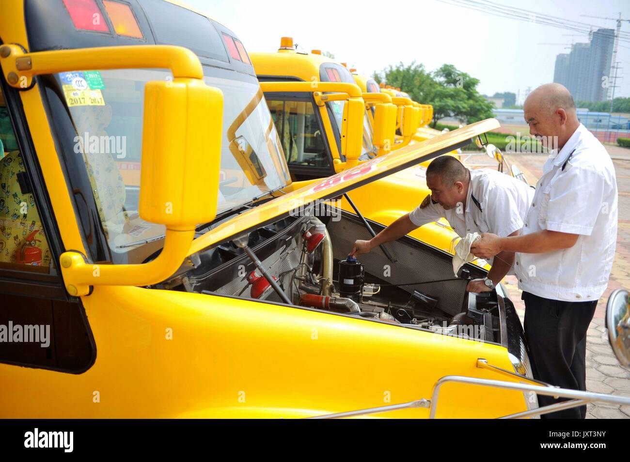 Qingdao, China's Shandong Province. 17th Aug, 2017. Staff check a school bus at a school bus company in Qingdao, Stock Photo