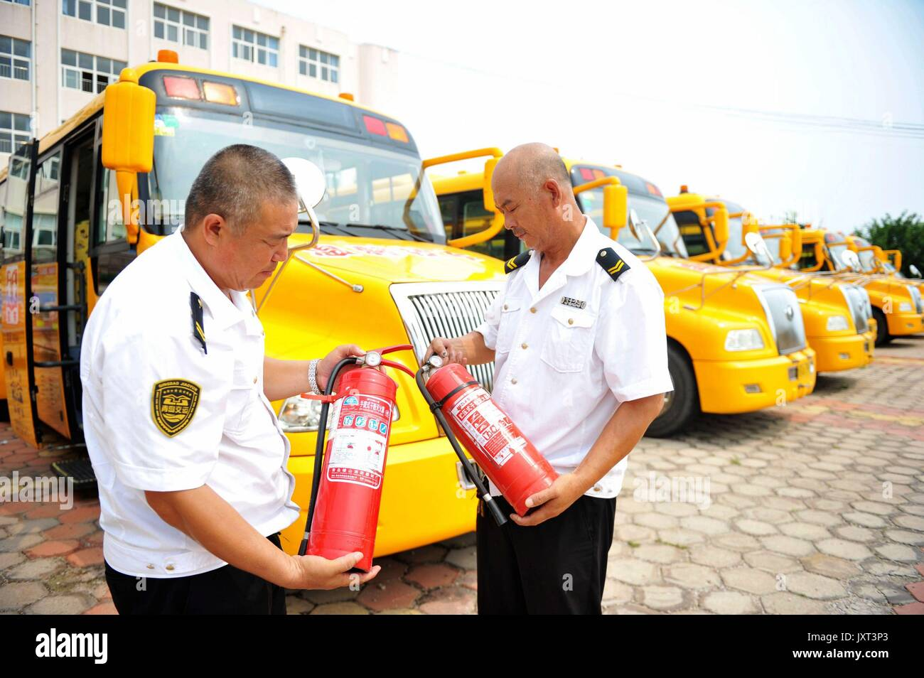 Qingdao, China's Shandong Province. 17th Aug, 2017. Staff check extinguishers used on school buses at a school bus Stock Photo