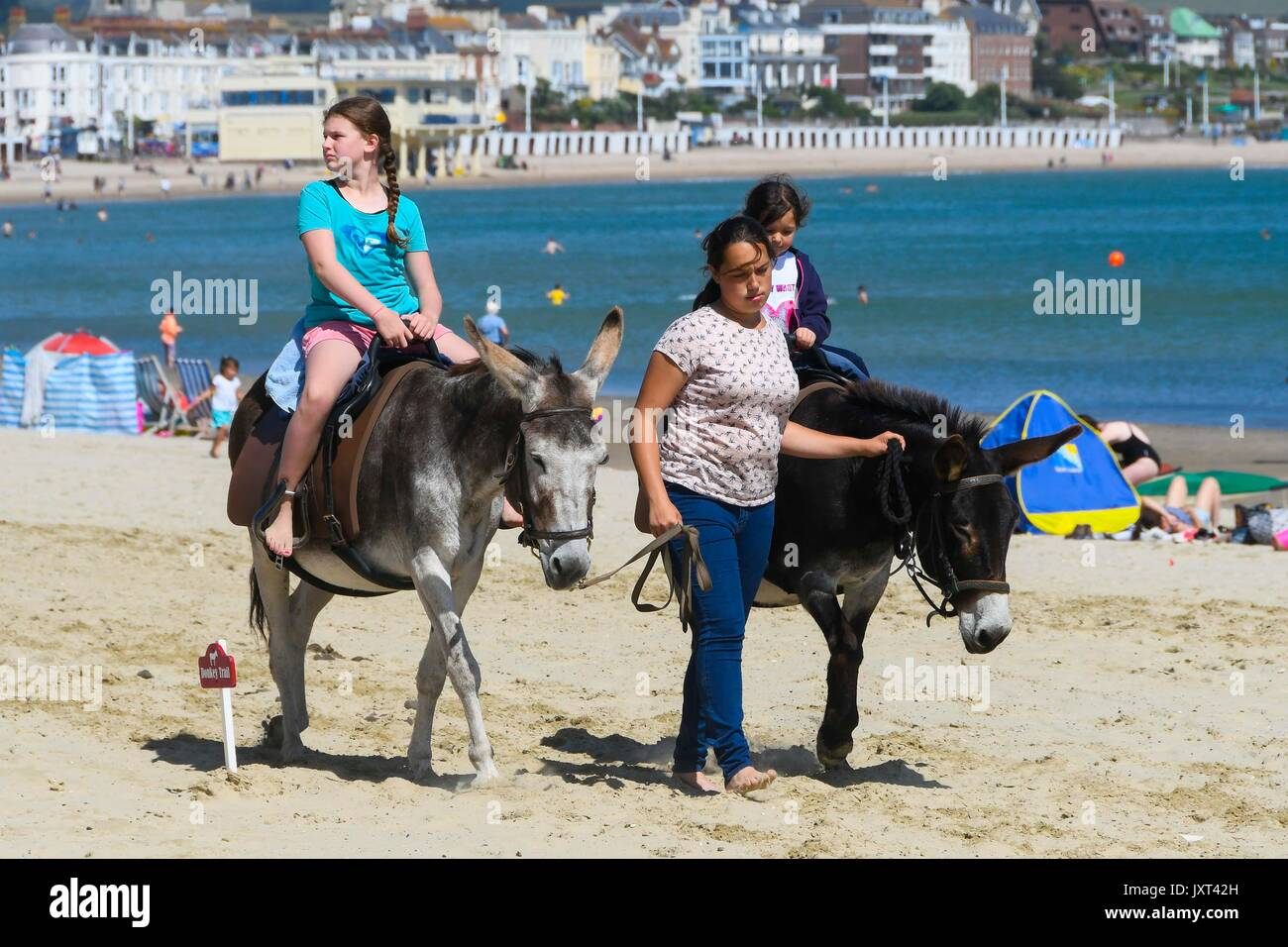 Weymouth, Dorset, UK. 17th Aug, 2017. UK Weather. Children having a donkey ride on the beach during the warm sunny Stock Photo