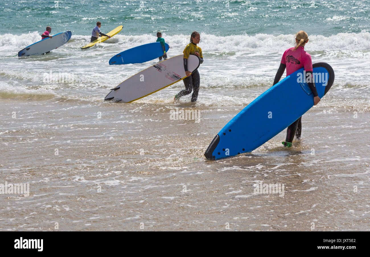 Boscombe, Bournemouth, Dorset, UK. 17th August, 2017. UK weather: sunny spells at Boscombe beach. Surfers enjoy the waves at the seaside carrying their surf boards into the sea. Credit: Carolyn Jenkins/Alamy Live News - Stock Image