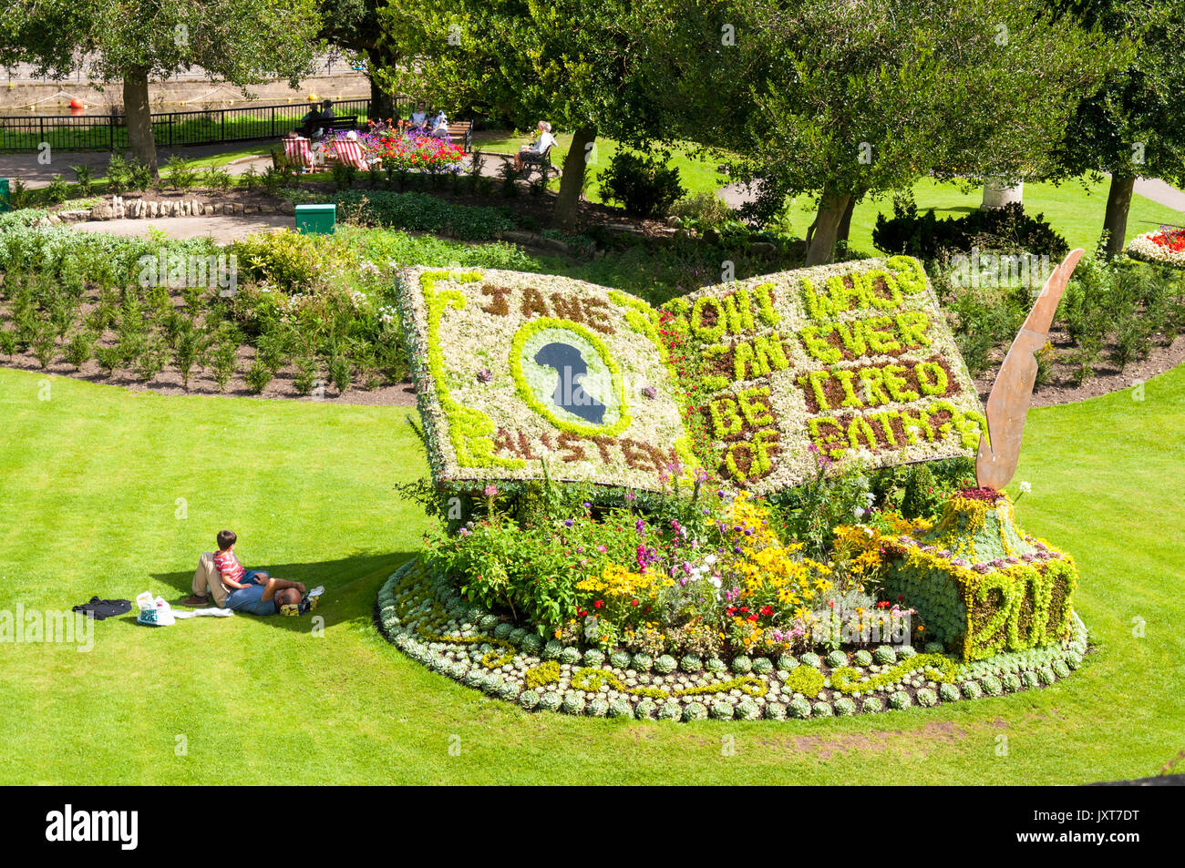 Bath, Somerset, UK. 17th Aug, 2017. UK Weather. People enjoy the sun and a floral tribute for the Annual International Jane Austen Festival in Bath UK. 2017 is an important bicentenary year being both the 200th anniversary of the Author's death and the publication of her two Bath novels Northanger Abbey and Persuasion, in Parade Gardens in the centre of the spa city. Credit: Richard Wayman/Alamy Live News - Stock Image