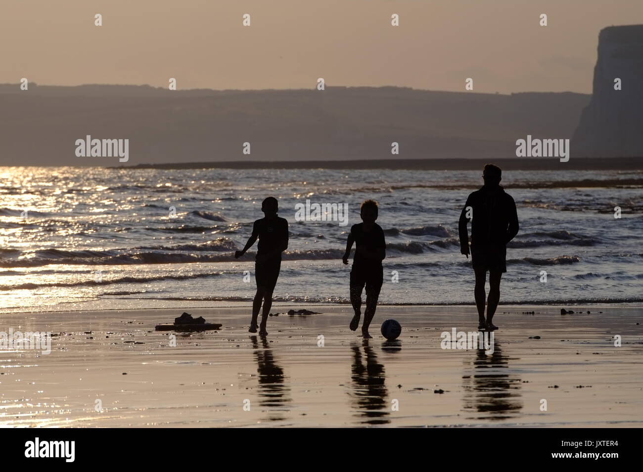 Father and sons playing ball games on a beach at sunset, Seven Sisters, South Downs National Park, East Sussex - Stock Image