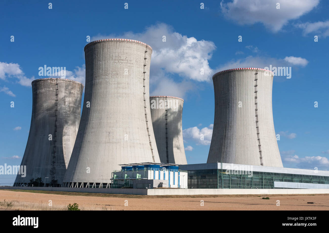Four  chimneys of nuclear power station in the summer day, cooling towers of nuclear plant against blue sky. - Stock Image