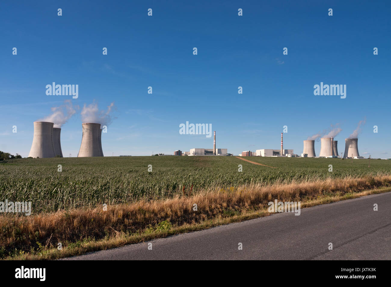 Aerial view of nuclear power station with cooling towers against blue sky, in the foreground green field. - Stock Image