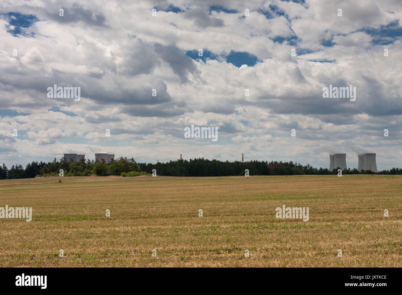 Aerial view of nuclear power station with cooling towers against cloudy sky, in the foreground  field. - Stock Image