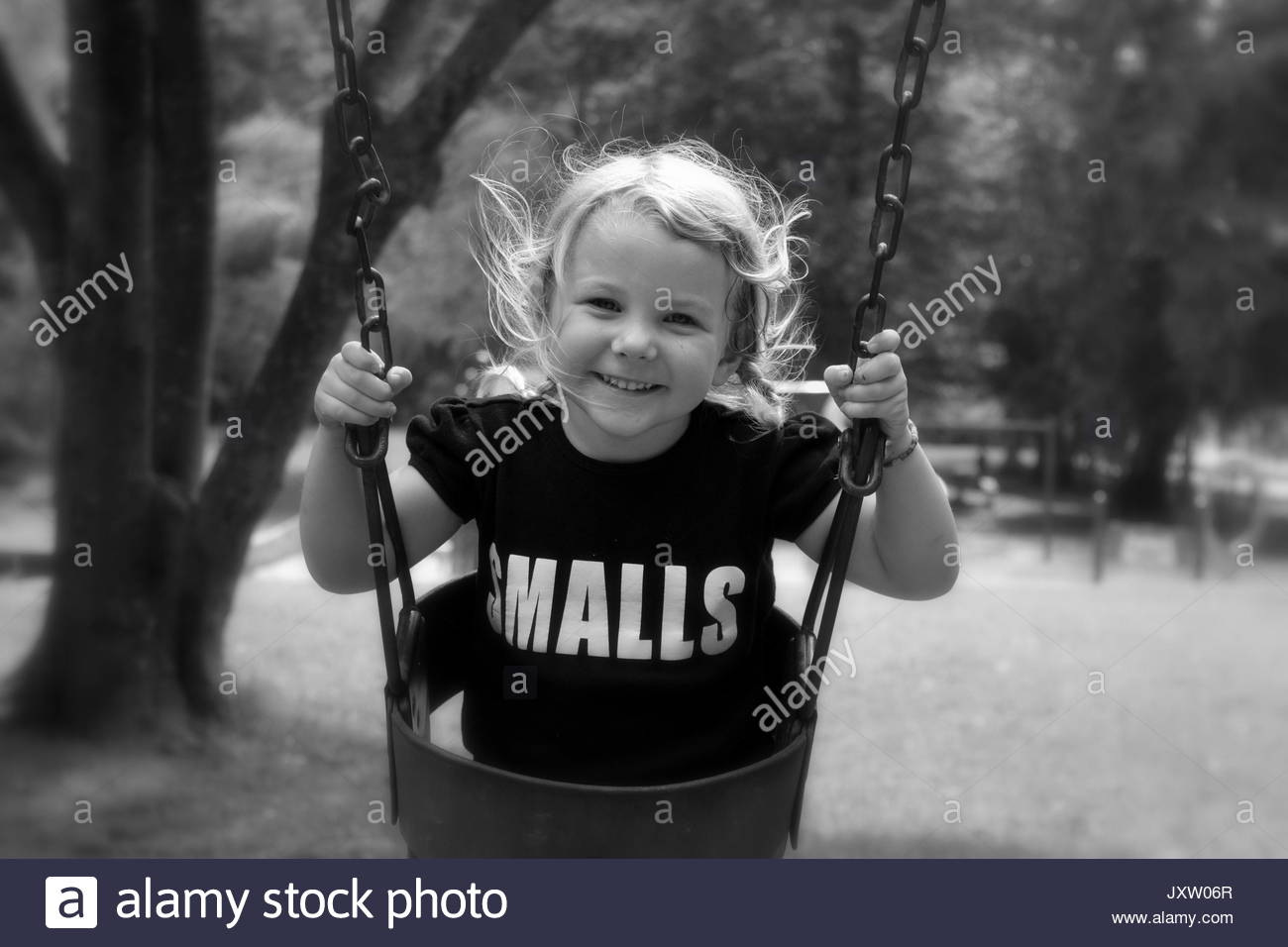 Smiling preschool girl swinging at a park - Stock Image