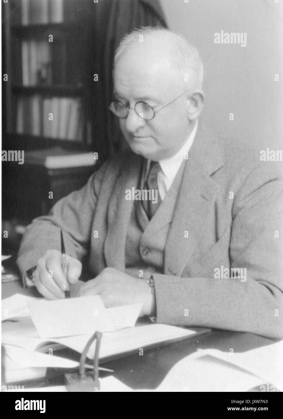 Joseph Sweetman Ames, Portrait photograph, Sitting at desk with pen in hand, Waist up, Three-quarter view, 1930. - Stock Image