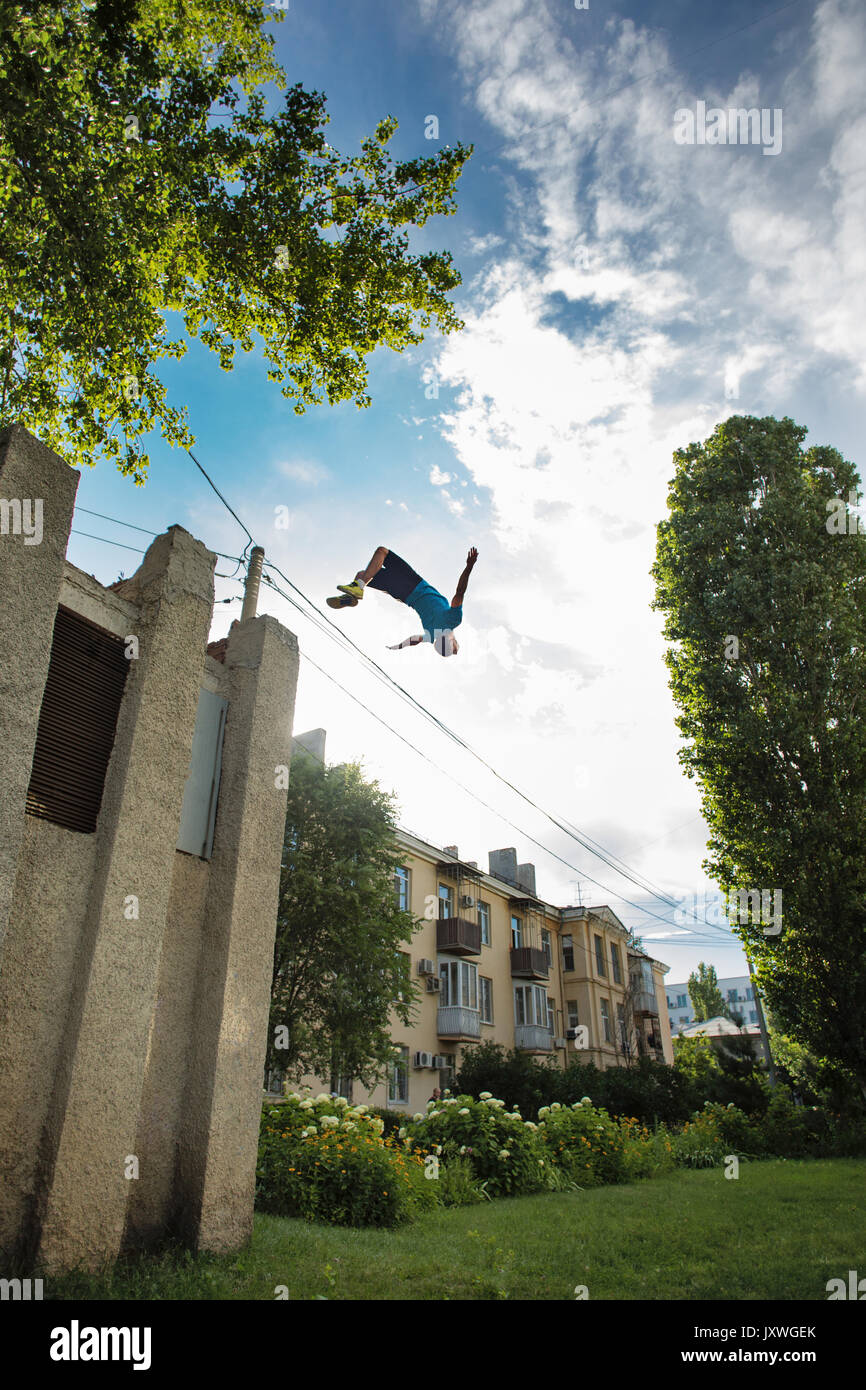 City parkour. The guy does the opposite somersault. Leap from the building. Shooting from the lower angle. Dexterity and extreme. - Stock Image