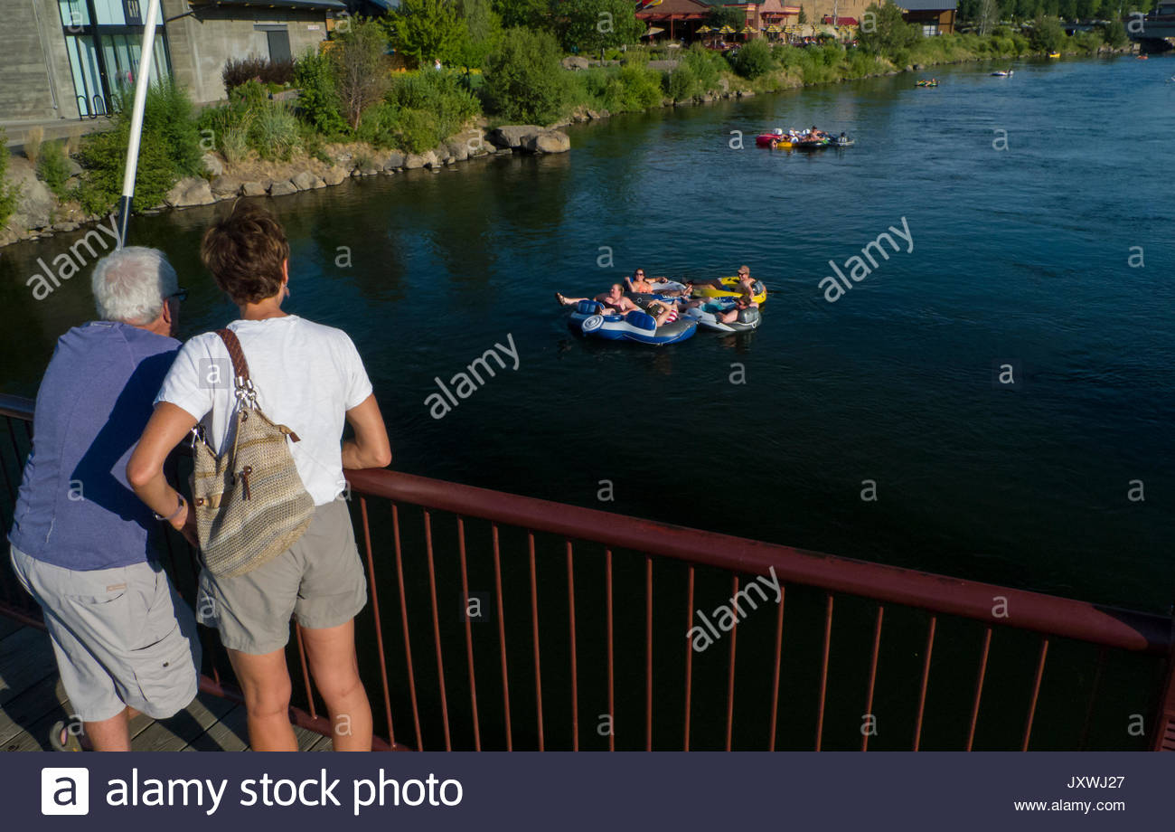 People watching people float by on inflatable pool toys from a pedestrian bridge spanning the Deschutes River, Old Stock Photo