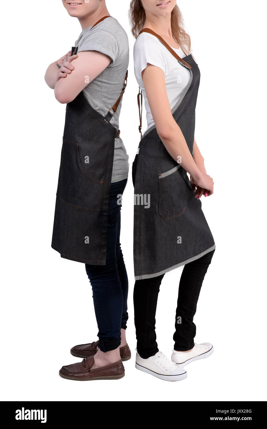 Young chefs or waiters man and woman posing, wearing aprons isolated on white background. Barista cafe coffee uniform. - Stock Image