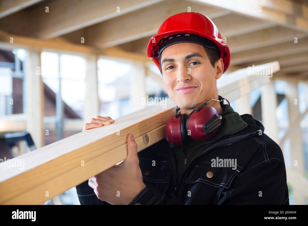 Carpenter Carrying Wood On Shoulder At Construction Site - Stock Image