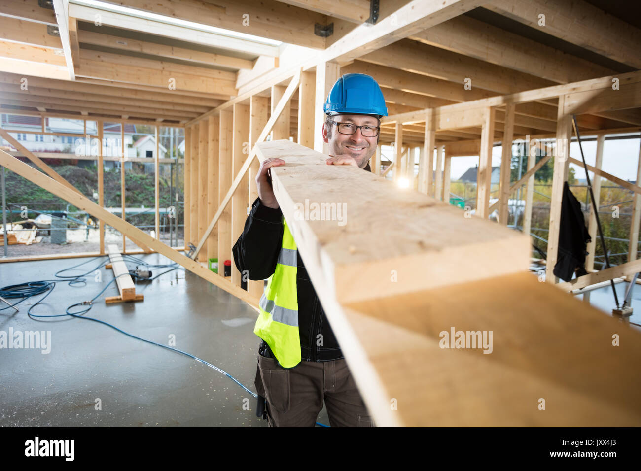 Portrait Of Confident Mature Carpenter Carrying Wood - Stock Image